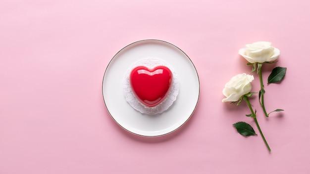 Plat lag samenstelling met rood hart cake en delicate witte roos. liefde of valentijnsdag concept. roze achtergrond. banner. kopieer ruimte