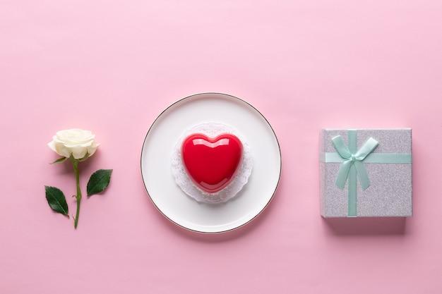 Plat lag samenstelling met rood hart cake, witte roos, geschenkdoos
