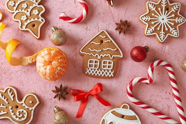 Plat lag samenstelling met smakelijke zelfgemaakte kerstkoekjes, mandarijn, snoepjes op roze. bovenaanzicht