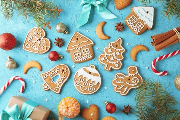 Plat lag samenstelling met smakelijke zelfgemaakte kerstkoekjes, op blauw. bovenaanzicht