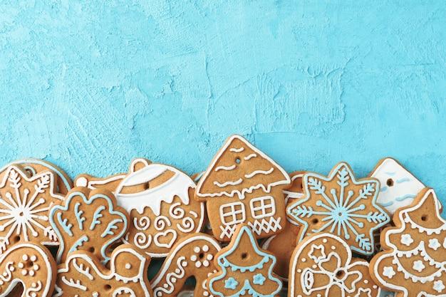 Plat lag samenstelling met smakelijke zelfgemaakte kerstkoekjes op blauw, ruimte voor tekst. bovenaanzicht