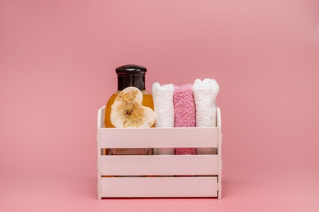 Plat lag samenstelling met spa cosmetica en handdoek op roze achtergrond.