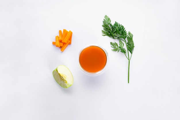 Plat lag samenstelling met vers wortelsap met gesneden wortelen en appel geïsoleerd