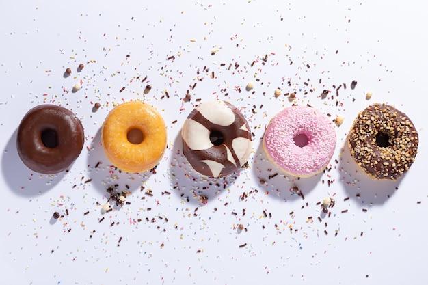 Plat lag samenstelling met verschillende donuts op witte achtergrond. bovenaanzicht.