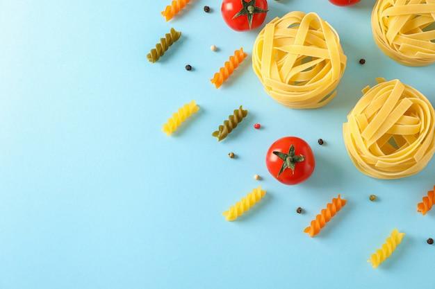 Plat lag samenstelling met verschillende pasta en tomaten op kleur achtergrond, ruimte voor tekst. droog ongekookte hele pasta