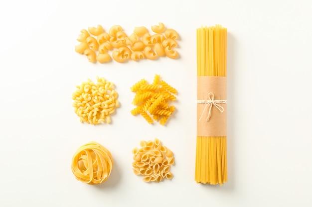 Plat lag samenstelling met verschillende pasta op witte achtergrond, ruimte voor tekst