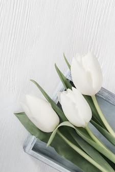 Plat lag samenstelling met witte tulpen op houten oppervlak tafel. lentebloemen voor dames of moederdag.