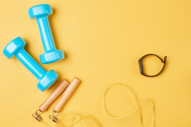 Plat lag samenstelling van blauwe halters, springtouw en fitness tracker op een gele achtergrond