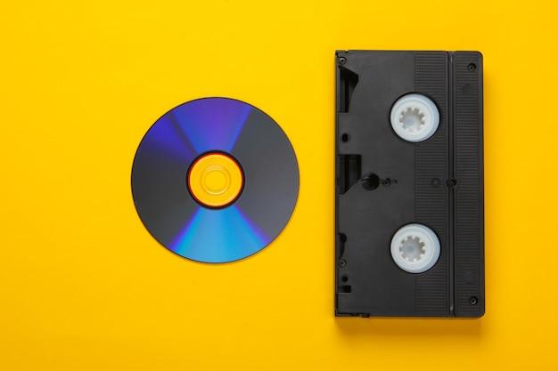 Plat lag samenstelling van cd-schijf, audiocassette op een geel. retro opslagmedia.