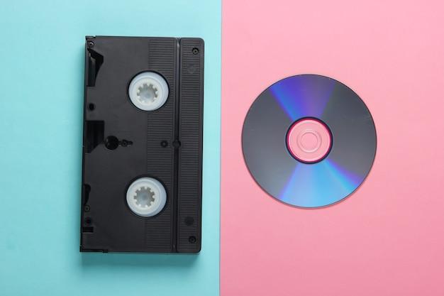 Plat lag samenstelling van cd-schijf, audiocassette op roze blauw. retro opslagmedia.