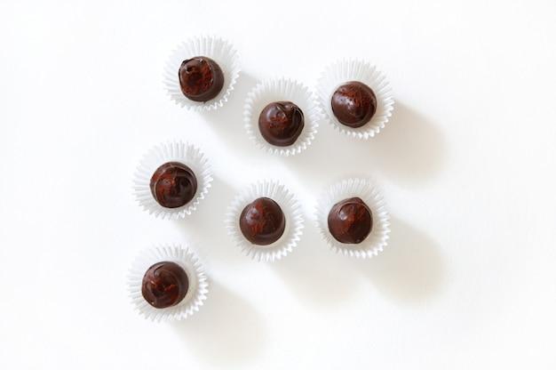 Plat lag samenstelling van chocoladetruffels bestrooid met gevriesdroogde aardbeien in papieren wikkels op een witte ondergrond