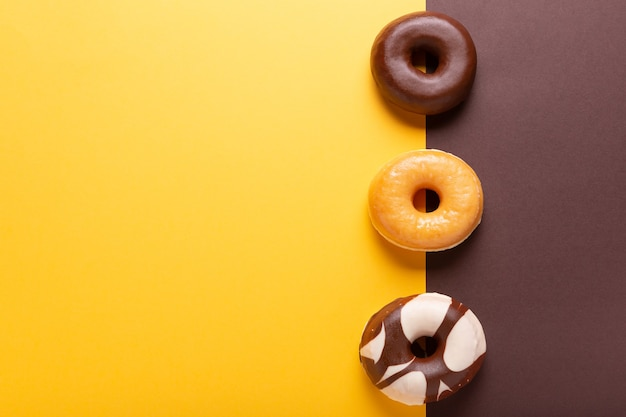 Plat lag samenstelling van drie donuts op bruine en gele achtergrond met copyspace.