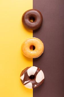 Plat lag samenstelling van drie donuts op bruine en gele achtergrond. verticaal formaat.
