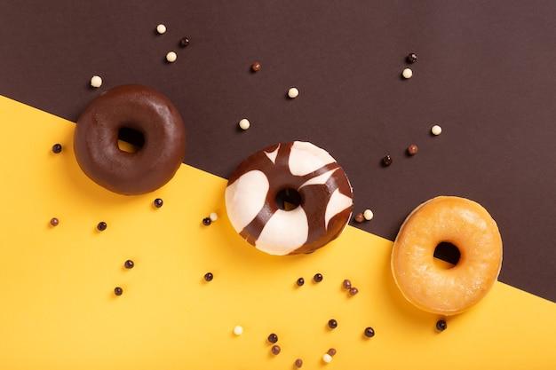 Plat lag samenstelling van drie donuts op bruine en gele achtergrond.