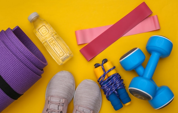 Plat lag samenstelling van fitness outfit, accessoires op gele achtergrond. gezonde levensstijl, sportconcept. bovenaanzicht