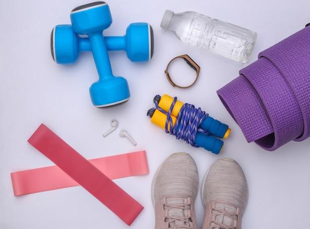 Plat lag samenstelling van fitness outfit, accessoires op witte achtergrond. gezonde levensstijl, sportconcept. bovenaanzicht