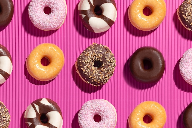 Plat lag samenstelling van gemengde donuts op roze achtergrond.