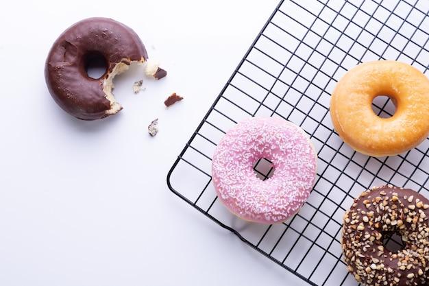 Plat lag samenstelling van gemengde donuts op witte achtergrond.