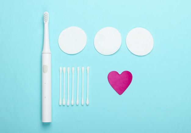 Plat lag samenstelling van hygiëneproducten. tandenborstel, wattenschijfjes, oorstokken op een blauwe achtergrond. bovenaanzicht