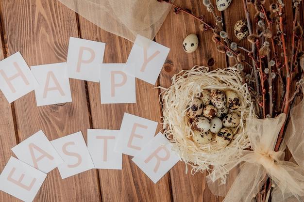 Plat lag samenstelling van kwarteleitjes en kaart tekst happy easter op houten tafel.