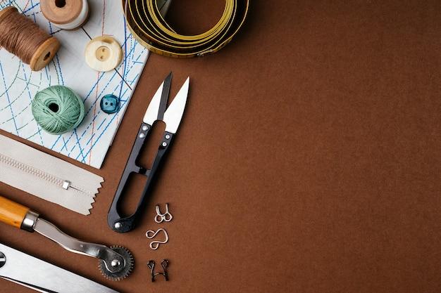 Plat lag samenstelling van naai-accessoires, schaar, patronen op een bruine achtergrond, bovenaanzicht, kopie ruimte.