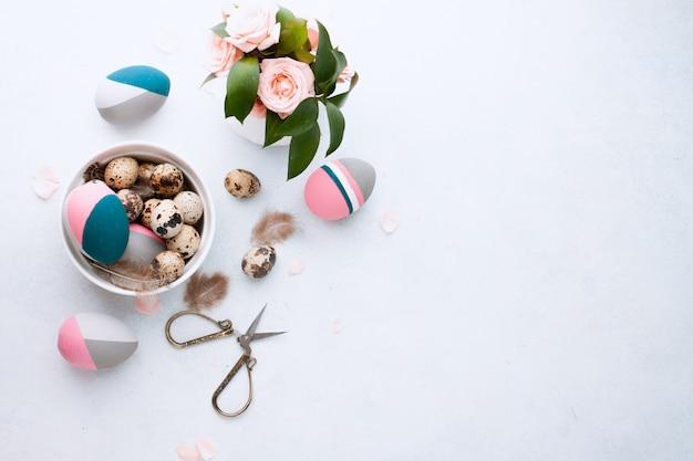 Plat lag samenstelling van natuurlijk geverfd kwartelei en kleur paaseieren liggend in lade op witte tafelmuur met veer en roze rozen. ruimte voor tekst
