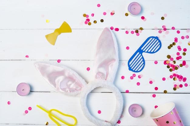 Plat lag samenstelling van verjaardag partij achtergrond met confetti, glas, maskers, haas oren