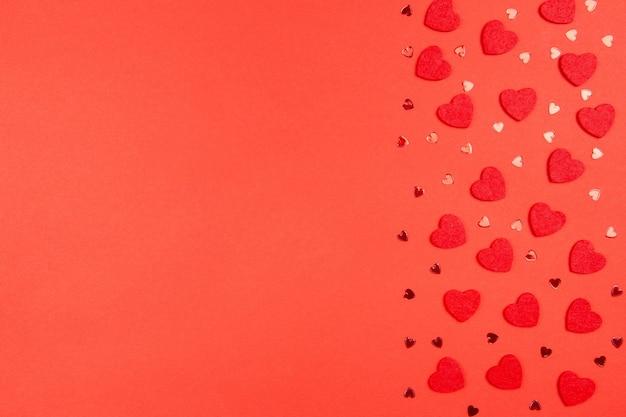 Plat lag samenstelling voor valentijnsdag, moederdag of bruiloft met rode harten op rood.