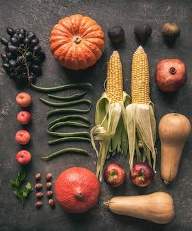 Plat lag seizoensgroenten en fruit op een grijze achtergrond