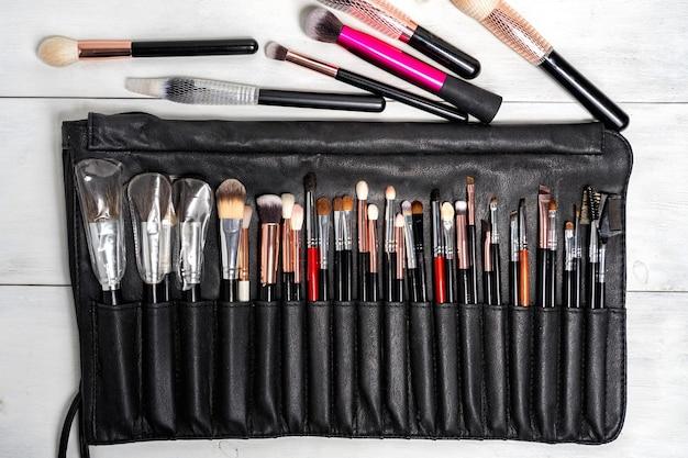 Plat lag set van zwarte make-up kwasten in een zwart lederen etui.