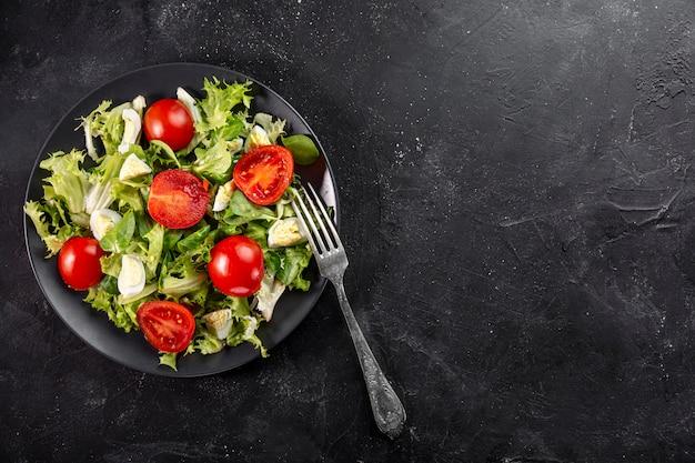 Plat lag smakelijke verse salade op zwarte plaat met kopie ruimte