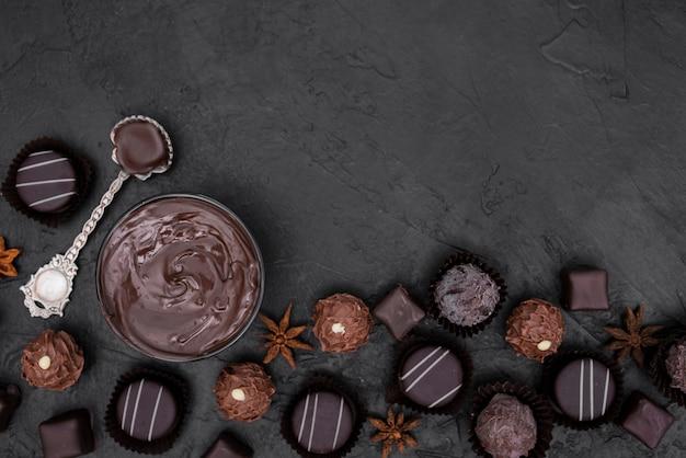 Plat lag snoepjes en gesmolten chocolade met kopie ruimte