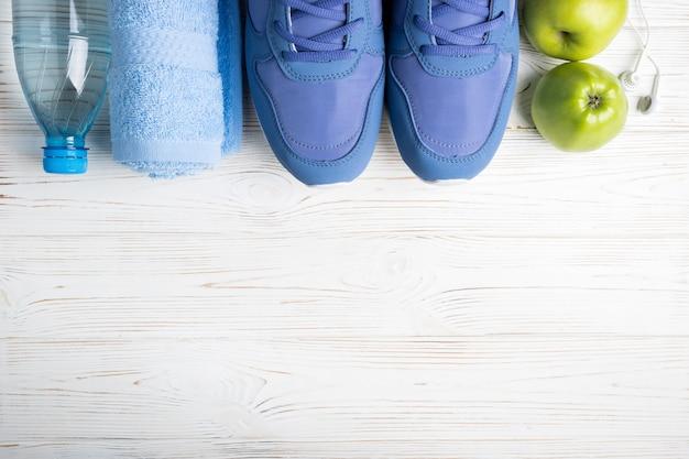 Plat lag sportschoenen, fles water, appels, handdoek en oortelefoons op wit.