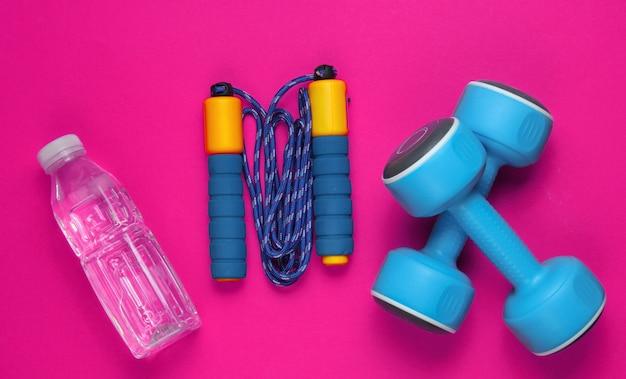 Plat lag stijl sport concept. halters, springtouw, fles water. sportuitrusting op roze