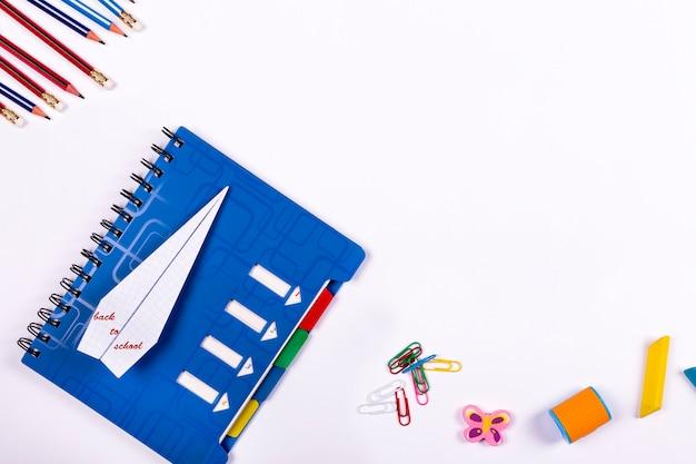 Plat lag terug naar school. school notebook, een vliegtuig van papier en accessoires