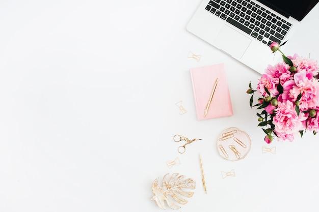 Plat lag thuiskantoor. vrouw werkruimte met laptop, roze pioenrozen boeket, gouden accessoires, roze dagboek op wit