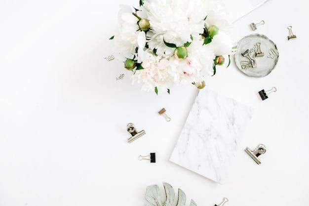 Plat lag thuiskantoor. vrouw werkruimte met witte pioenroos bloemen boeket, accessoires, marmeren dagboek op wit