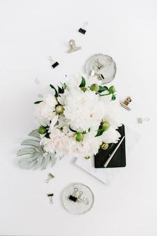 Plat lag thuiskantoor. vrouw werkruimte met witte pioenroos bloemen boeket op wit