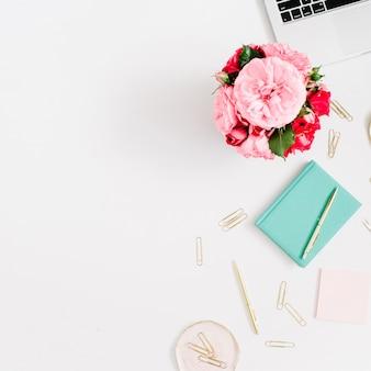 Plat lag thuiskantoor. vrouwelijke werkruimte met laptop, roze en rode rozenboeket, gouden toebehoren, muntdagboek op wit