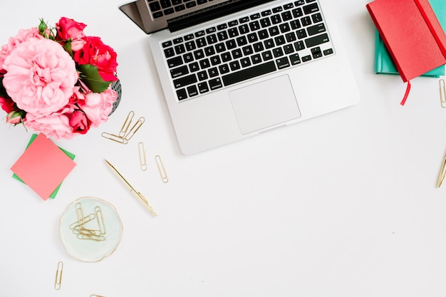 Plat lag thuiskantoor. vrouwelijke werkruimte met laptop, roze en rood rozenboeket, gouden toebehoren, rood en muntdagboek op wit