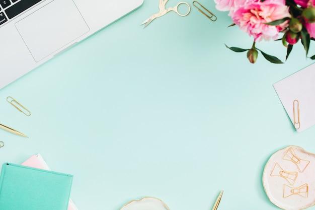 Plat lag thuiskantoor. vrouwelijke werkruimte met laptop, roze pioenrozen boeket, gouden accessoires, roze en mint dagboek op munt