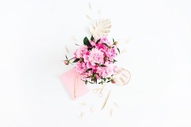 Plat lag thuiskantoor. vrouwelijke werkruimte met roze pioenrozen boeket, gouden accessoires, roze dagboek op wit