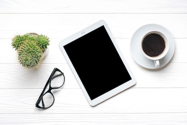 Plat lag thuiskantoor werkruimte. tablet, glazen, kopje koffie, sappig op witte houten tafel