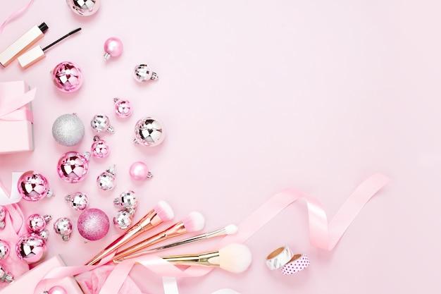 Plat lag vakantie achtergrond met kerstbal, cadeau, lint en decoraties in pastel roze kleur. platliggend, bovenaanzicht