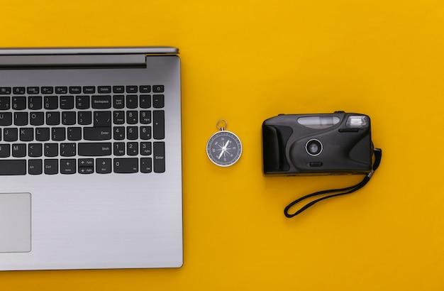 Plat lag vakantie vakantie en reizen schaven concept. laptop en camera, kompas op gele achtergrond. bovenaanzicht