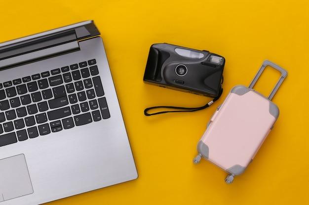 Plat lag vakantie vakantie en reizen schaven concept. laptop en mini plastic reiskoffer, camera op gele achtergrond. bovenaanzicht