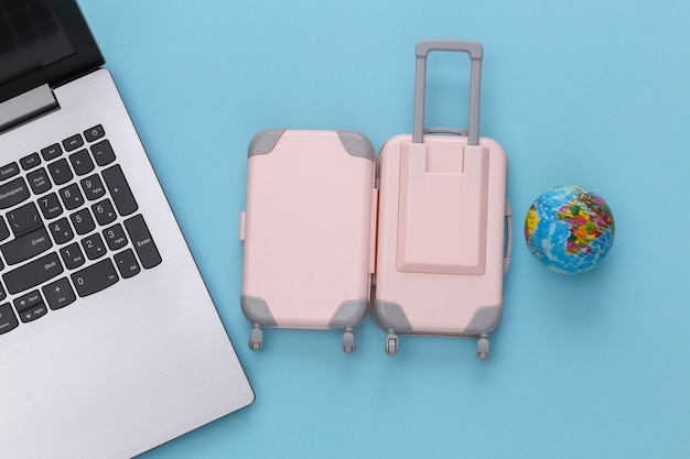Plat lag vakantie vakantie en reizen schaven concept. laptop en mini plastic reiskoffer, globe op blauwe achtergrond. bovenaanzicht