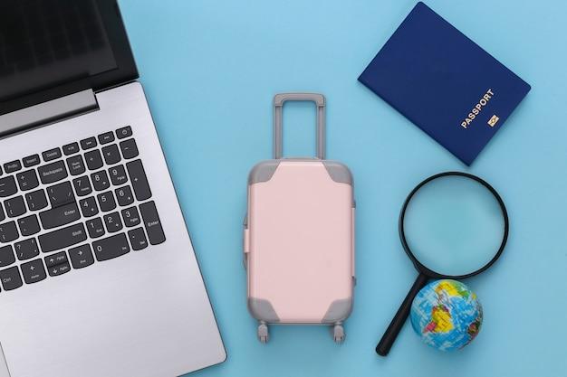Plat lag vakantie vakantie en reizen schaven concept. laptop en mini plastic reiskoffer, globe, paspoort op blauwe achtergrond. bovenaanzicht