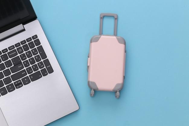 Plat lag vakantie vakantie en reizen schaven concept. laptop en mini plastic reiskoffer op blauwe achtergrond. bovenaanzicht