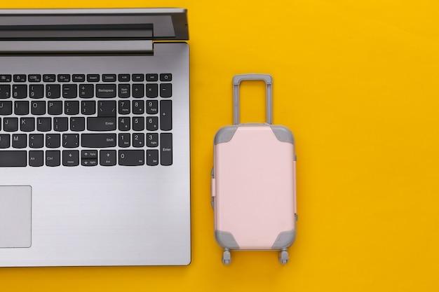 Plat lag vakantie vakantie en reizen schaven concept. laptop en mini plastic reiskoffer op gele achtergrond. bovenaanzicht